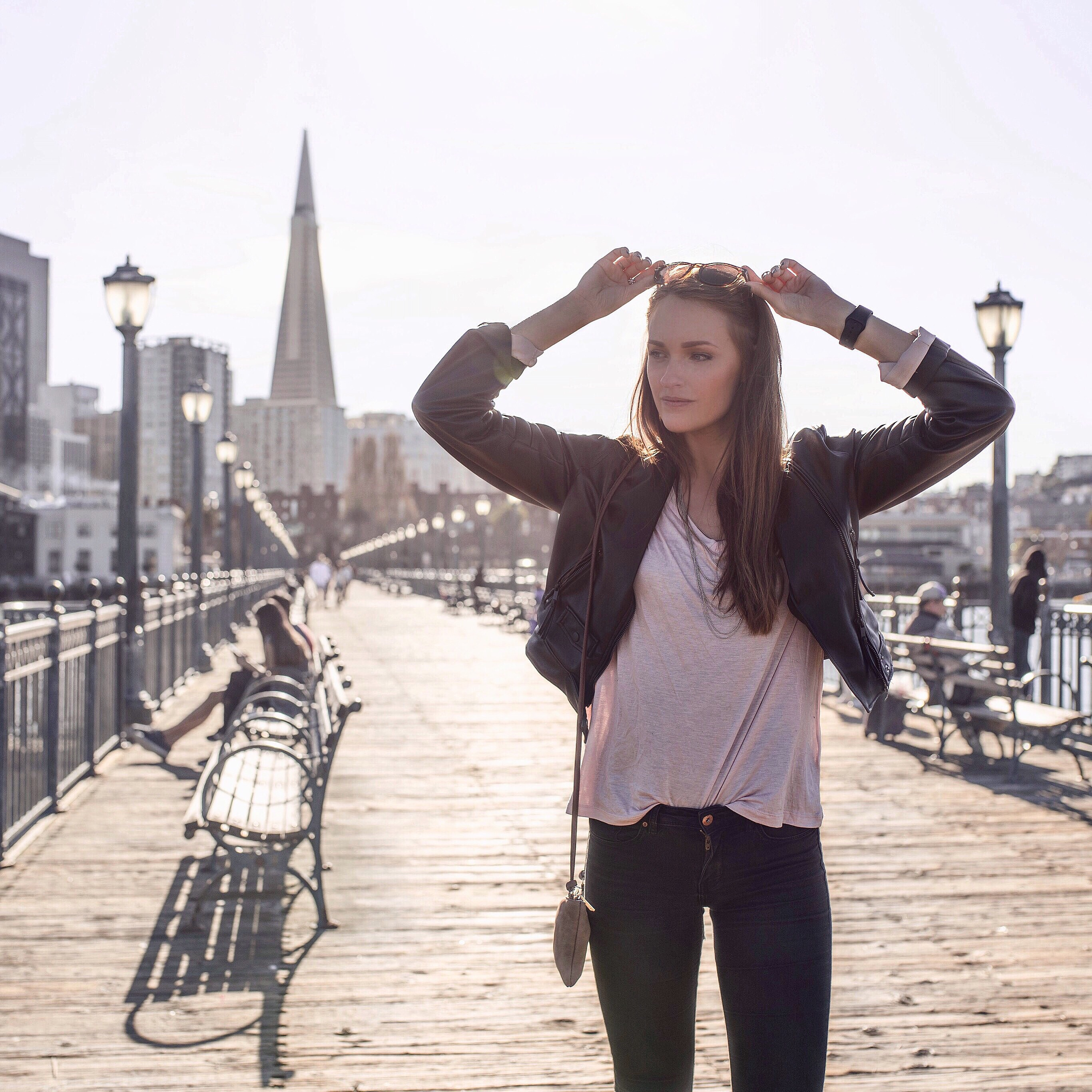 Alexandra Andersson ståendes på en bro med stad i bakgrunden