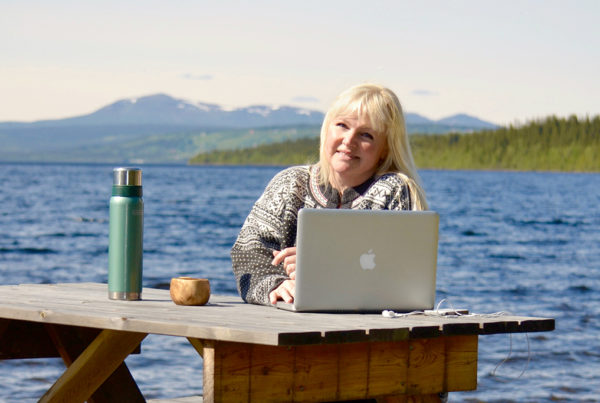 Pernilla Öberg vid ett träbord utomhus framför havet med sin Mac-dator