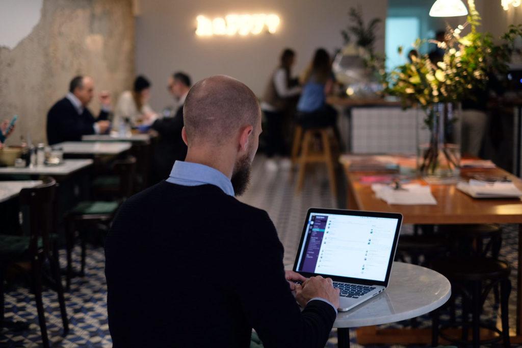 Christoffer från Svenska Nomader sitter med Slack uppe på Bowls & bar i Lissabon