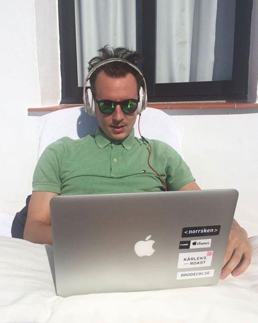 Daniel arbetar utomhus med sin laptop i soligt klimat