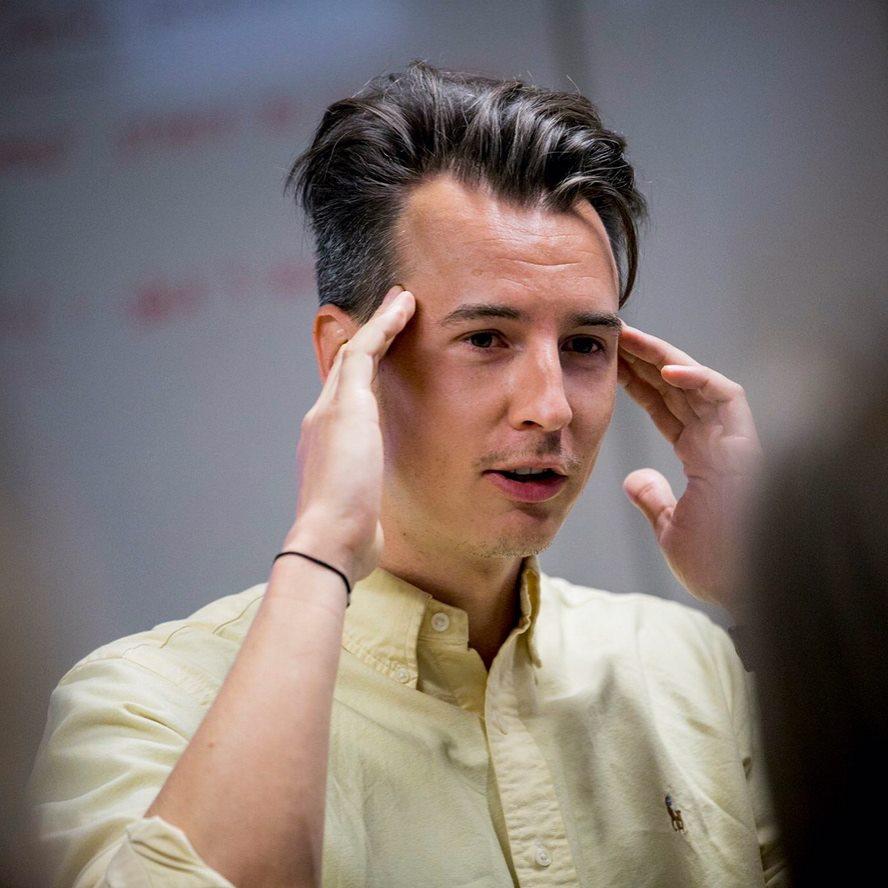 Daniel Brodecki i gul skjorta pekar med bägge händer mot sitt huvud.
