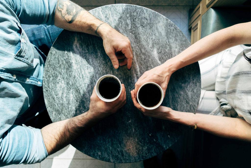 Två okända människor i möte med en kopp kaffe