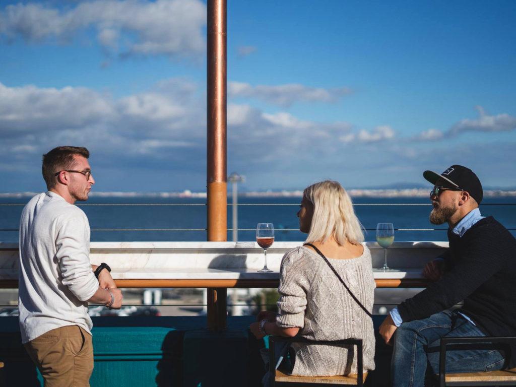 En grupp om tre diskuterar över ett glas vin
