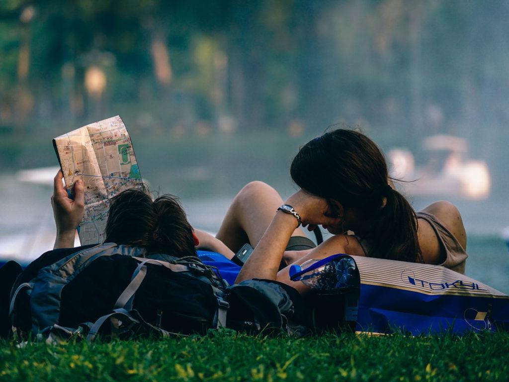 Kille och tjej ligger ner på sina ryggsäckar och läser en karta