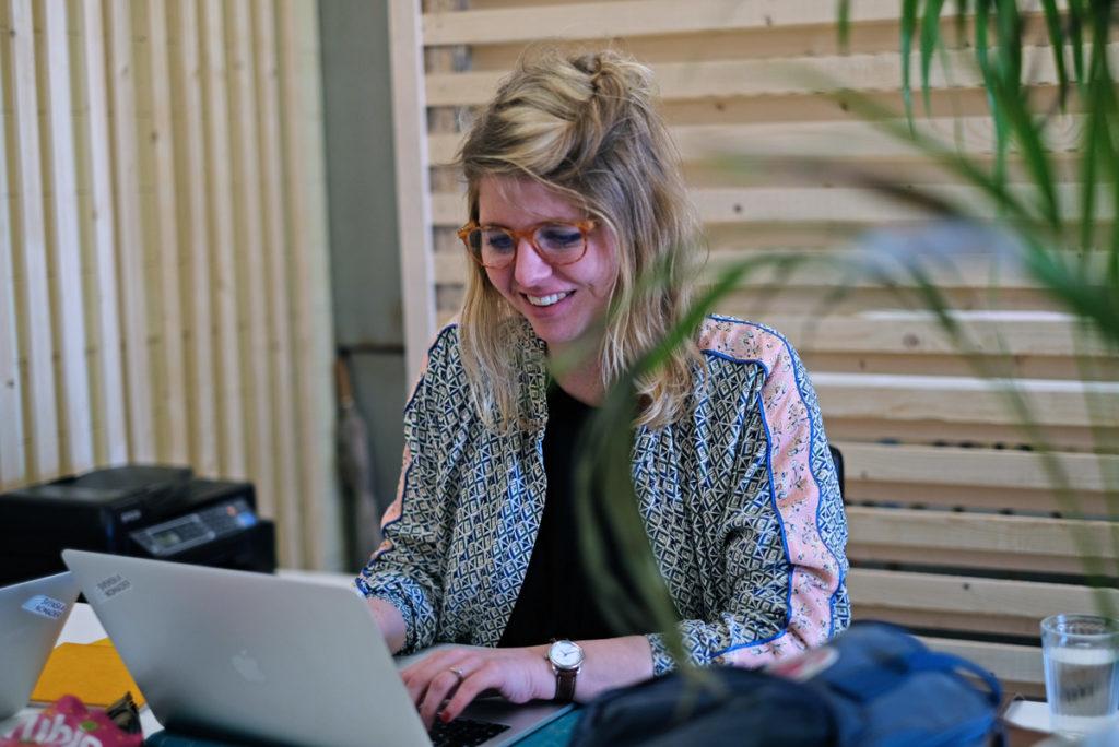 Emelie jobbar på distans med en laptop från ett kontor i Lissabon.