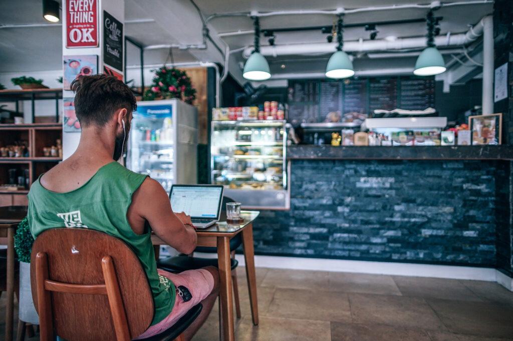 Kille sitter på café i Linne och jobbar på ett café
