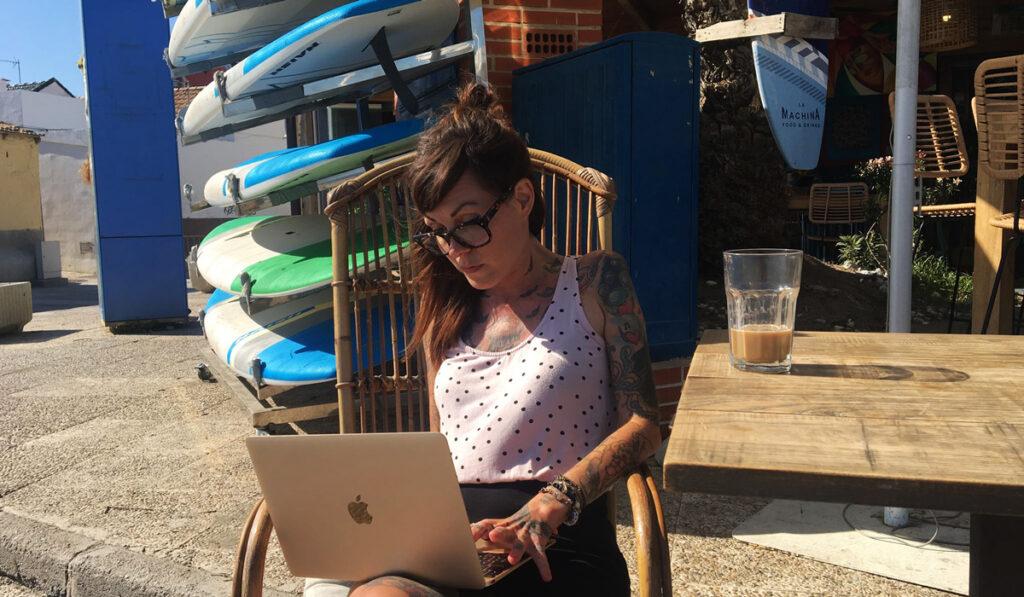 Åsa sitter på en stol med en dator i sitt knä