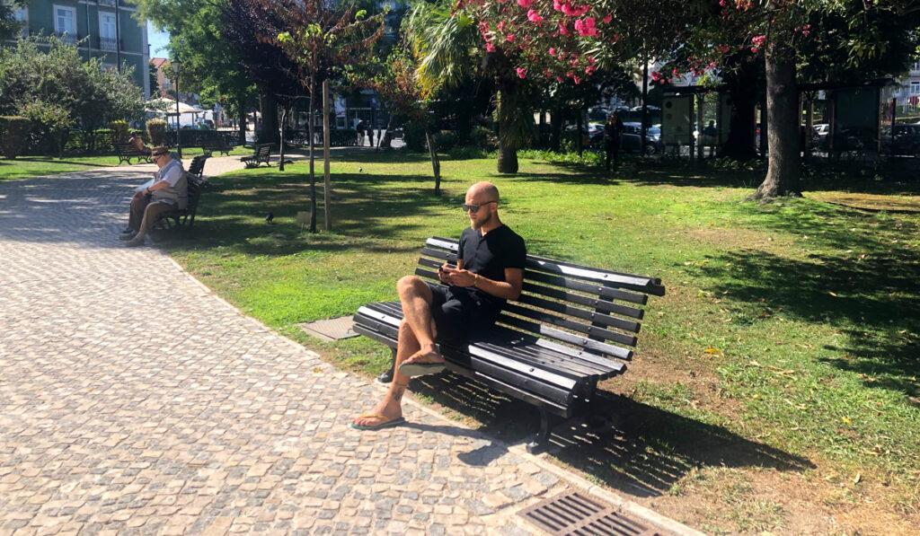 Christoffer på en parkbänk med sin mobil i Jardim braancamp
