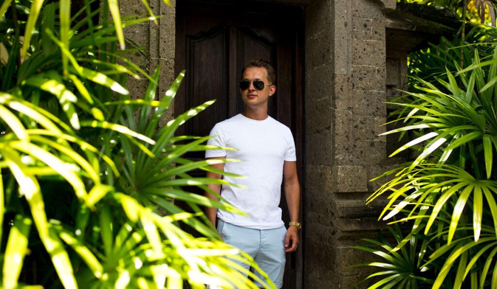 Jimmy Björnhård står lutad mot en vägg i djungelliknande natur