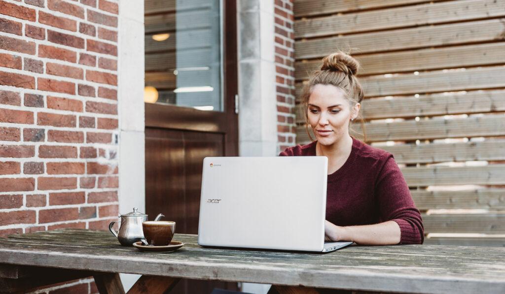 Kvinna sitter utomhus och jobbar med sin dator och sitt te
