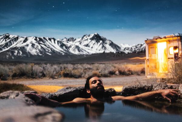 Man ligger i en naturlig källa och badar med berg i bakgrunden