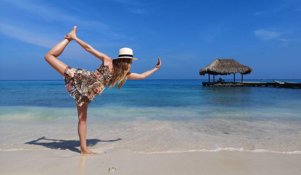 Emelie Ering på en strand hållandes sin fot i högt läge