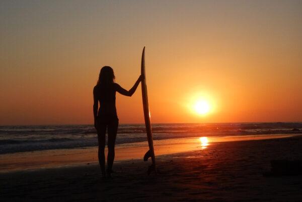 Emelie Ering med surfbräda i horisonten