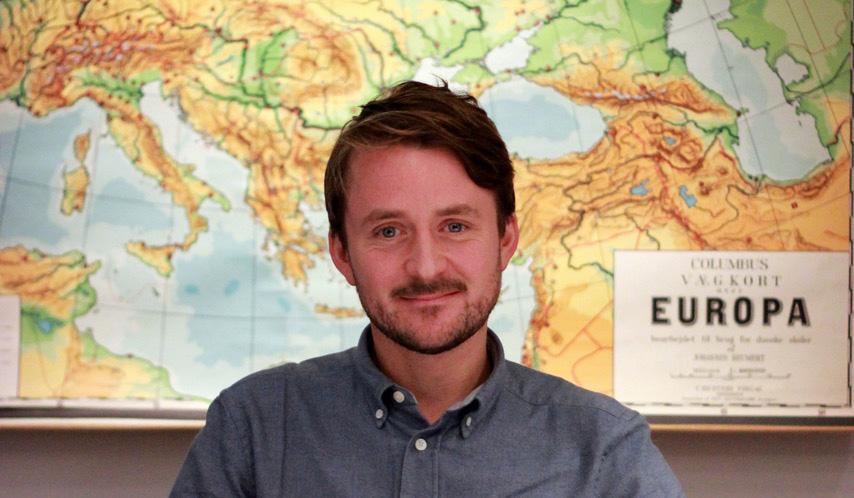 Ted Valentin sitter framför en karta av Europa