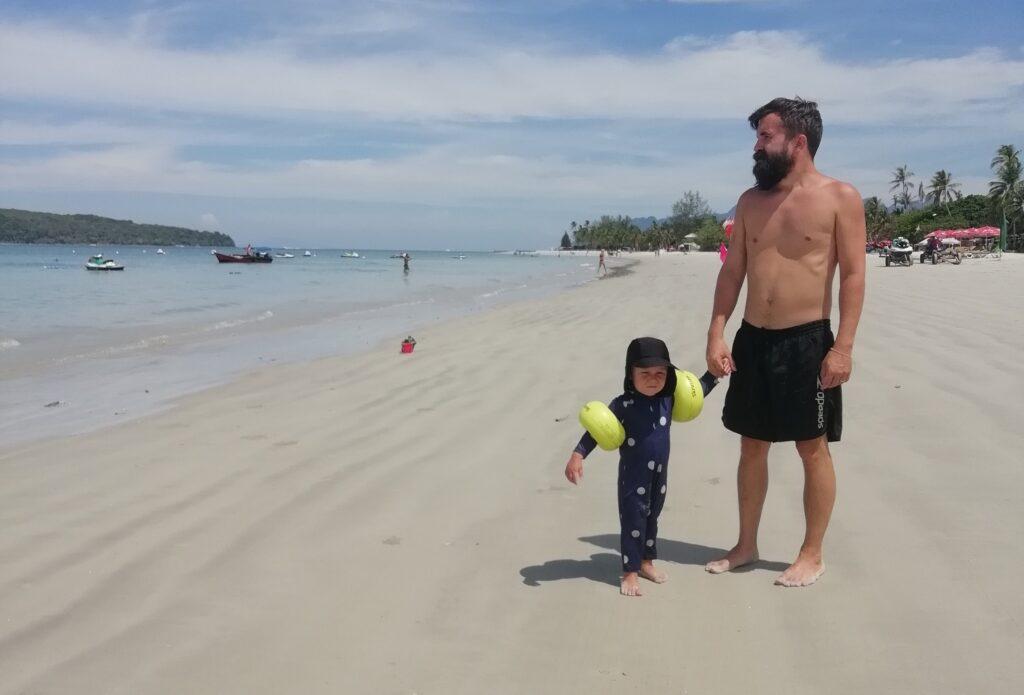 pappa på stranden med sin tvååriga son