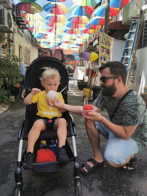 Pappa äter glass med sin son som sitter i barnvagn under massa färgglada paraplyer