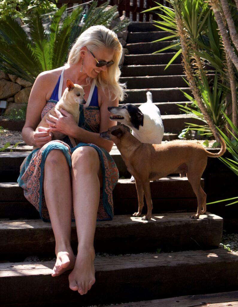 kvinna sitter på en trappa med tre hundar