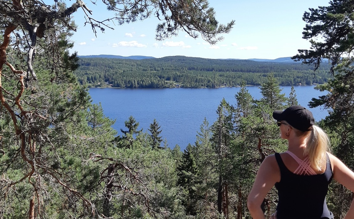 kvinna står och kollar på utsikten över en sjö