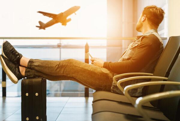 En kille sitter på en stol på flygplatsen med sin mobil och tittar drömskt ut mot ett lyftande plan.