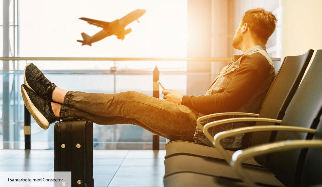 Kille sitter i stol på flygplats och tittar drömskt ut mot ett flygplan som lyft