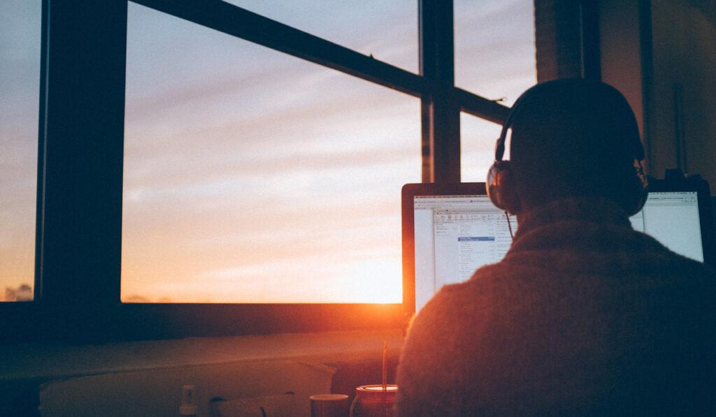 Man som sitter framför dator i solnedgången