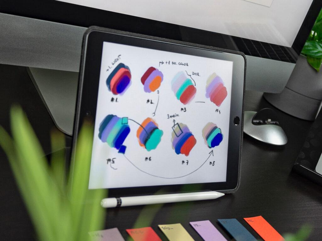 Webbyrå tittar på webbdesign till en hemsida via en ipad, dator och små färgglada post-it-lappar