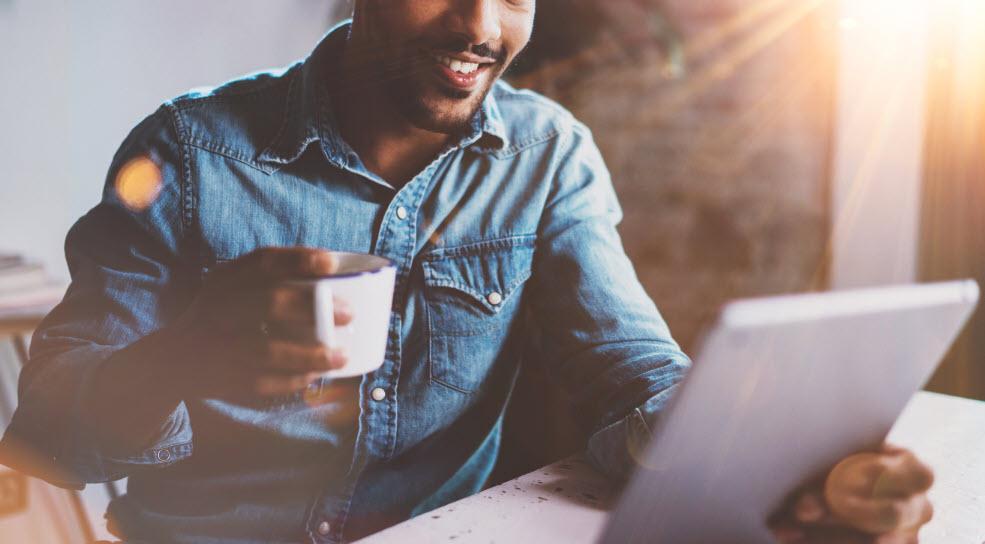 Kille sitter med en kaffekopp i ena handen och en tablet i andra.
