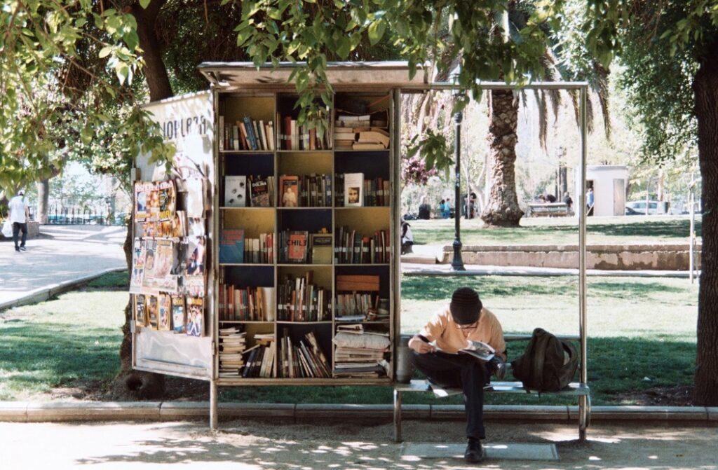 en pojke sitter och läser vid en busshållplats med en bokhylla