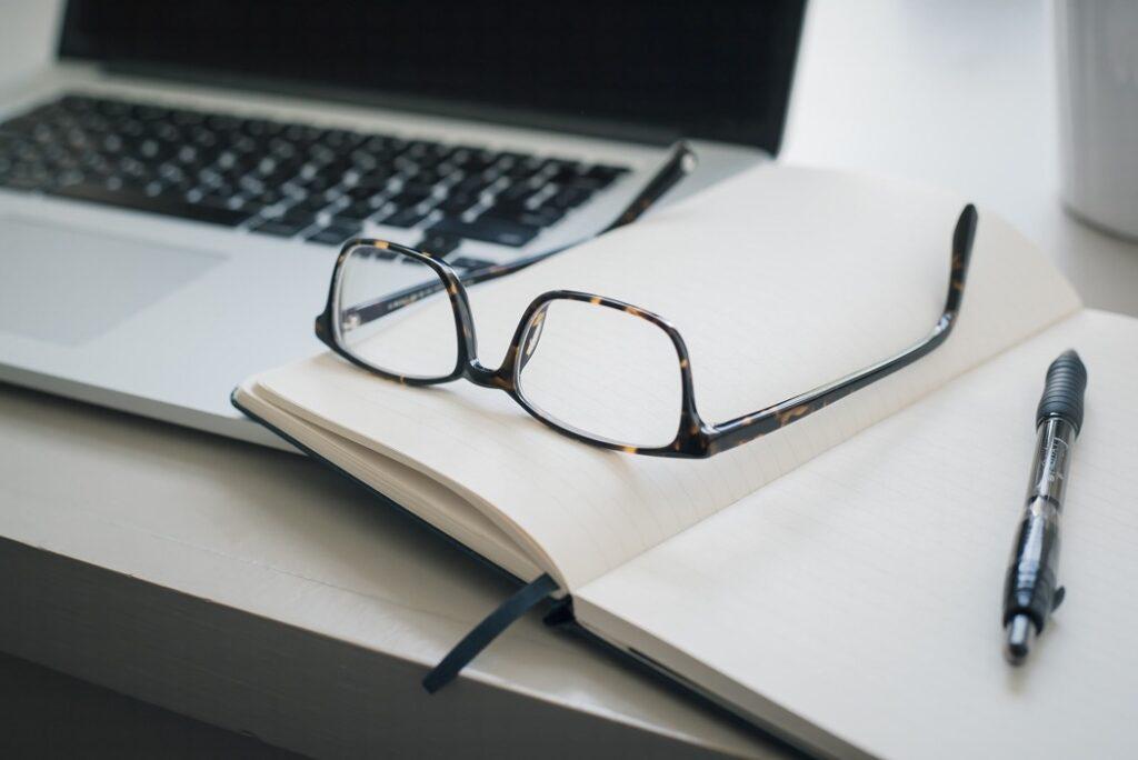 anteckningsblock, dator, glasögon