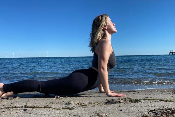 Denise Elina i en yogaposition på stranden