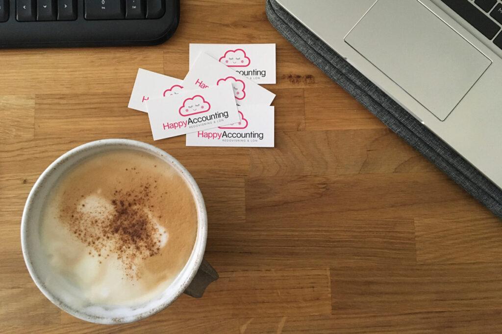 Visitkort från Happy accounting bredvid dator och en kopp kaffe