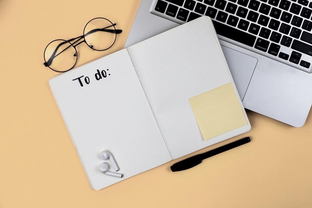 ett anteckningsblock där det står to-do, en laptop och ett par glasögon