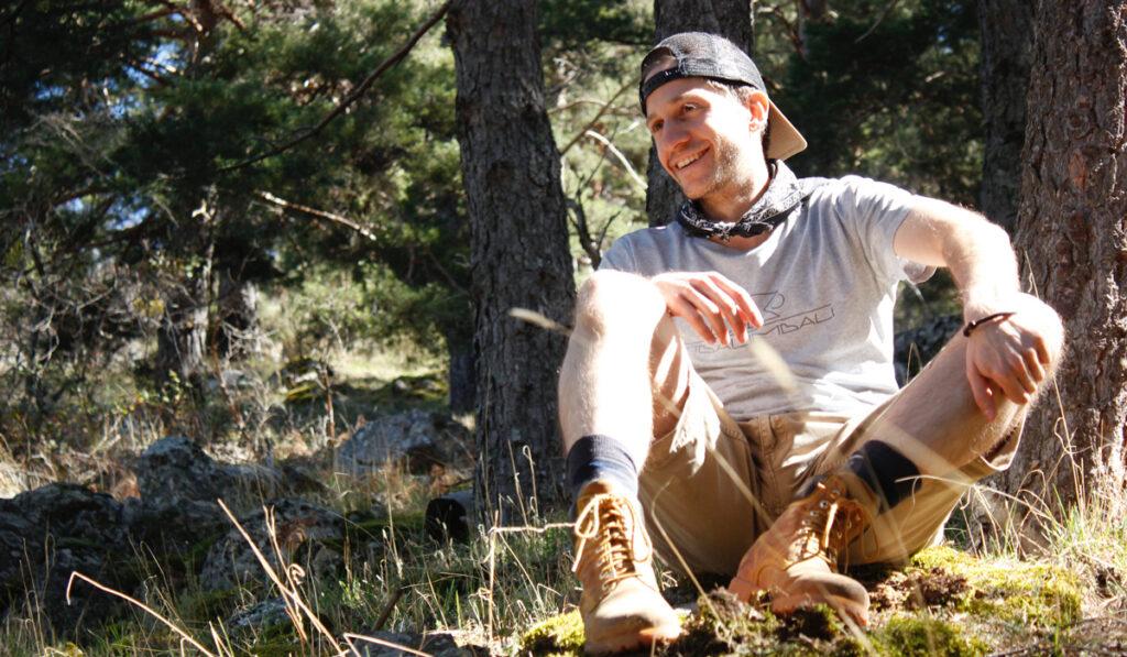 Man sitter i skogen och i solen med hippa vandringsklädder