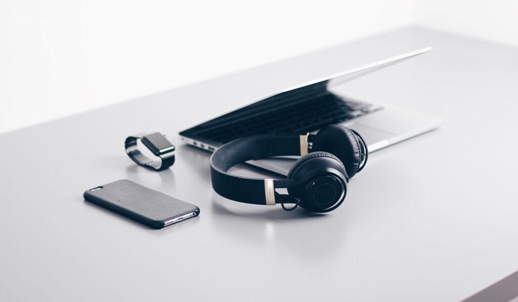 En dator, ett par hörlurar, en smartwatch och en telefon ligger på ett bord