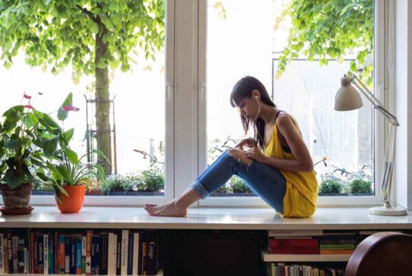 En tjej sitter med sin telefon i en fönsterkarm