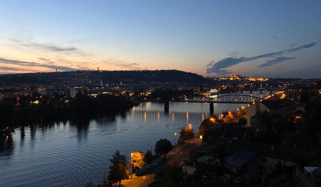 Utsikt över Prag och en bro under kvällstid
