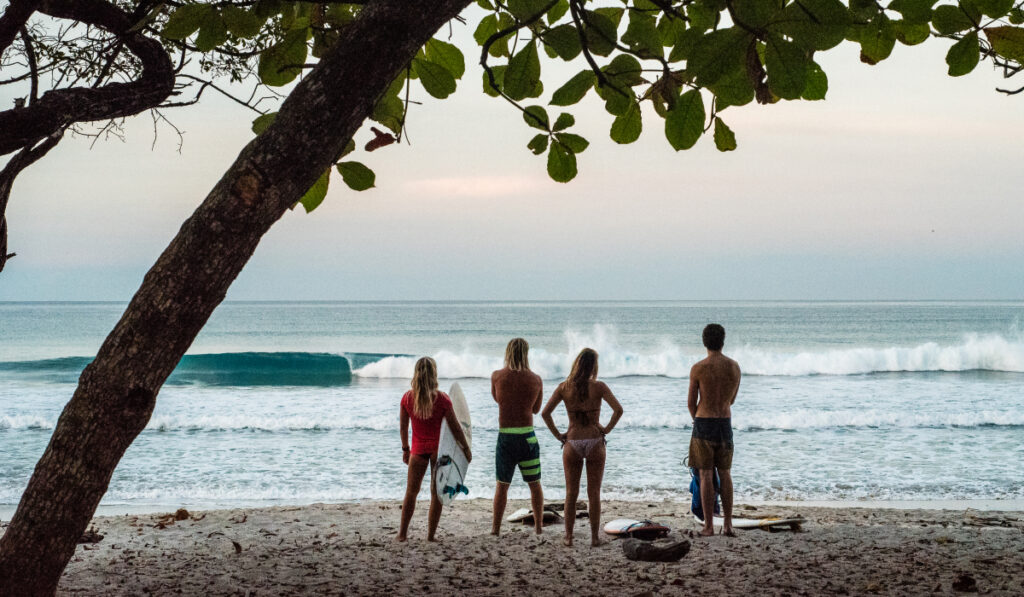 4 surfare tittar ut över vågorna från stranden i Sri Lanka