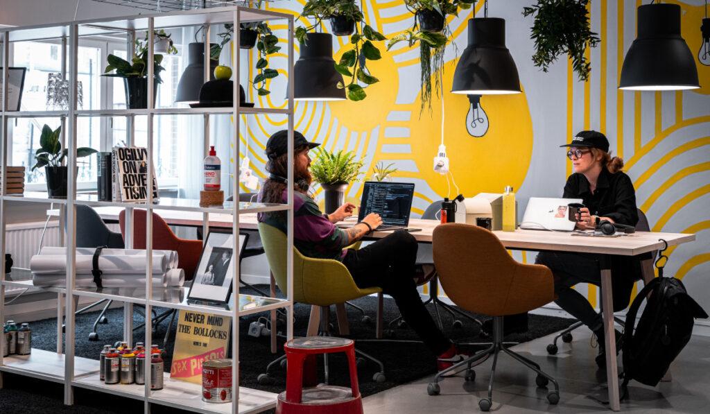 Två kreatörer arbetar från Kaffe & Wifi-ytan på Creative Hub STHLM