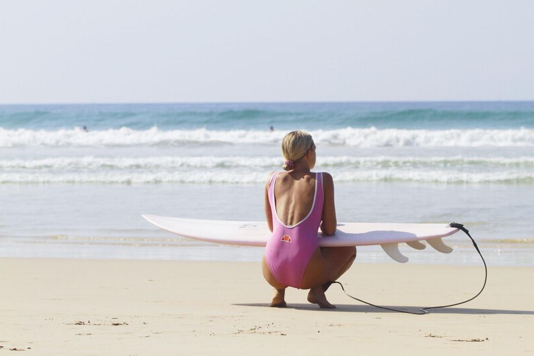 Linda på stranden med surbrädan i knäet
