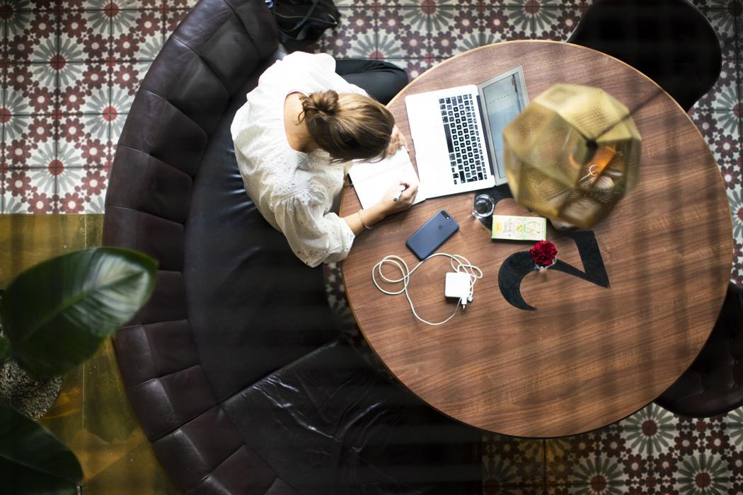 Kvinna arbetar på sin laptop från Scandic lobby